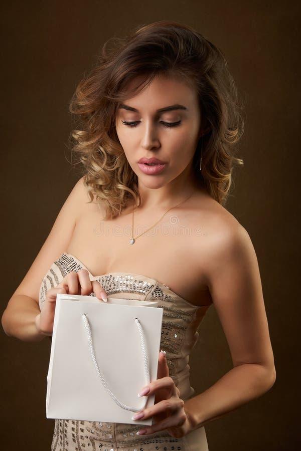 年轻美女画象有购物带来的反对黑暗的背景 库存照片