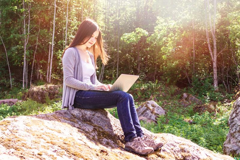 年轻美女研究膝上型计算机,当坐在森林自由职业者的概念时的一个大岩石 库存照片