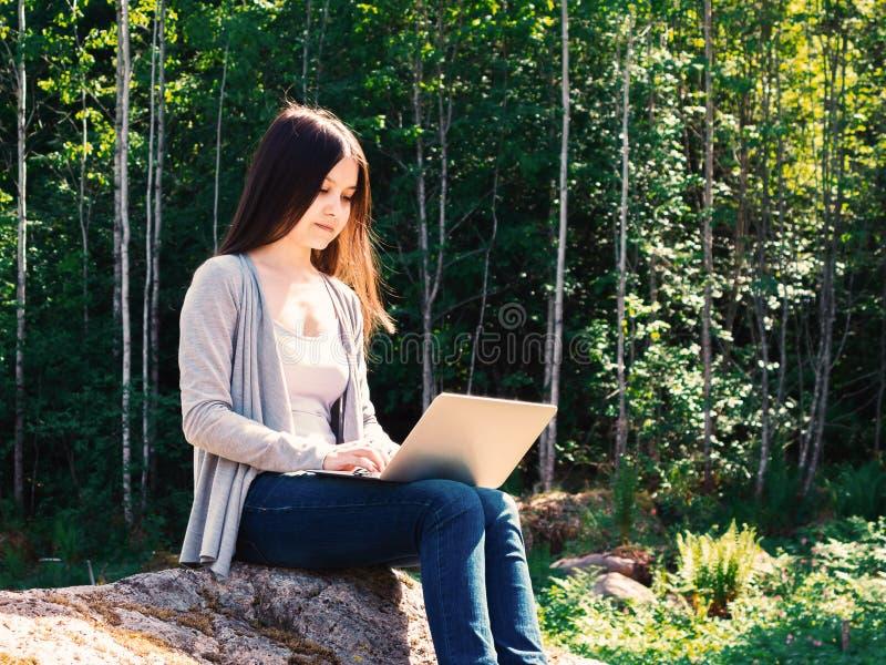 年轻美女研究膝上型计算机,当坐在森林自由职业者的概念时的一个大岩石 免版税库存照片