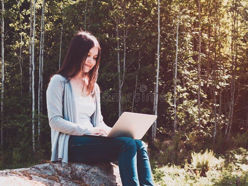 年轻美女研究膝上型计算机,当坐在森林自由职业者的概念时的一个大岩石 免版税库存图片
