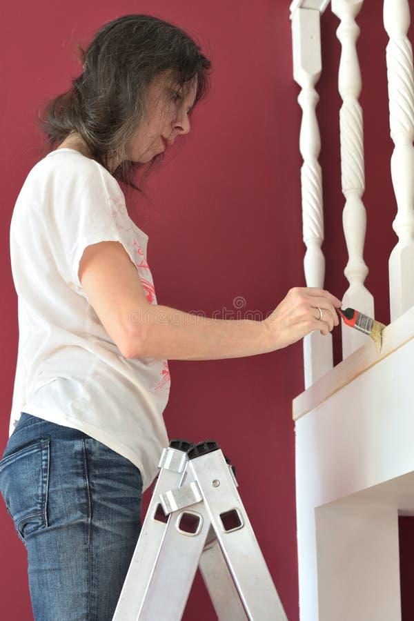 年轻美女绘画壁架ballustrade白色与刷子 库存图片