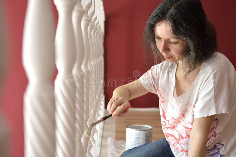 年轻美女绘画壁架ballustrade白色与刷子 库存照片