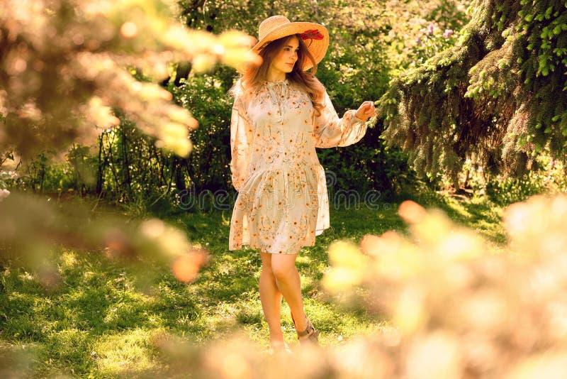 年轻美女跳舞在公园 帽子和轻的夏天礼服 库存照片