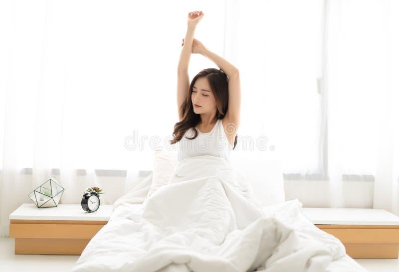 年轻美女醒愉快在舒展在舒适的床上的健康睡眠以后 晚安,早晨好,新的天, 库存图片