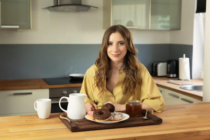 年轻美女食用早餐在家在厨房 图库摄影