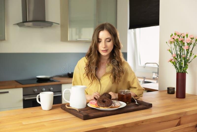 年轻美女食用早餐在家在厨房 库存图片