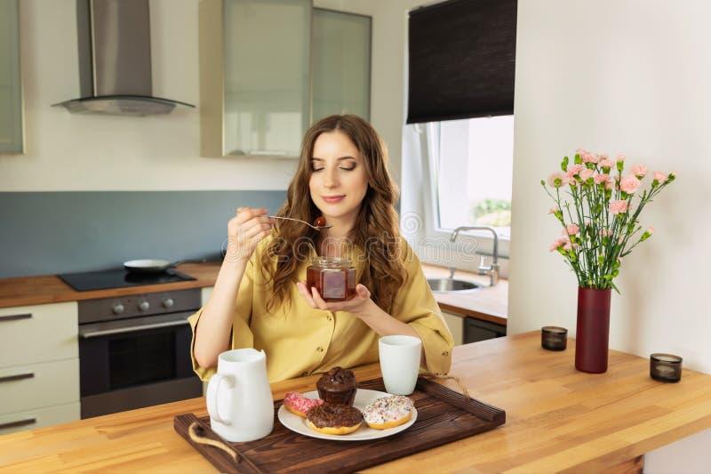 年轻美女食用早餐在家在厨房 库存照片