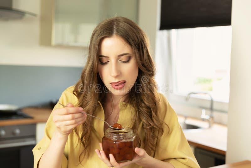 年轻美女食用早餐在家在厨房 免版税库存照片