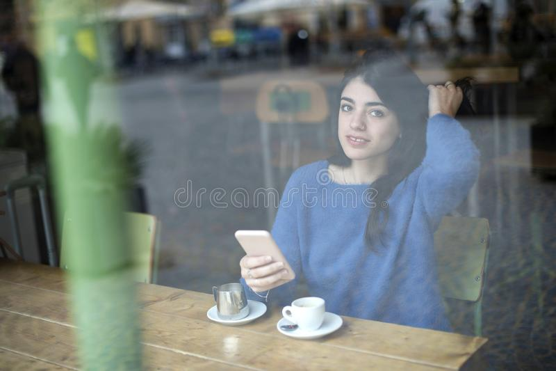年轻美女饮用的咖啡和使用她智能手机坐室内在都市咖啡馆 咖啡馆城市生活方式 偶然画象  免版税库存照片
