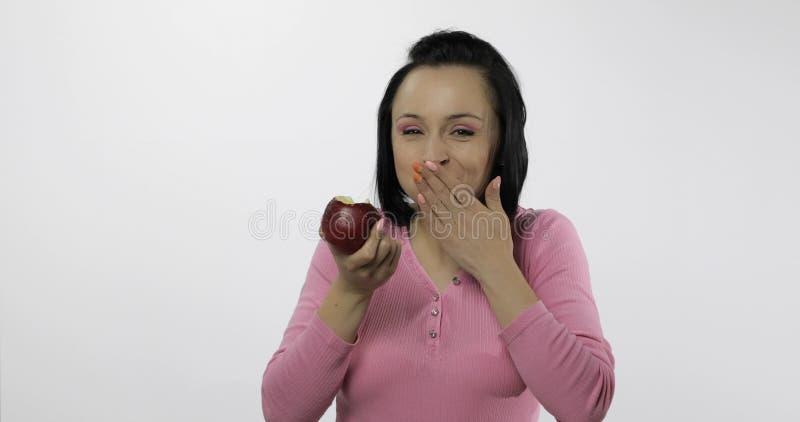 年轻美好吃红色苹果 r 免版税库存照片