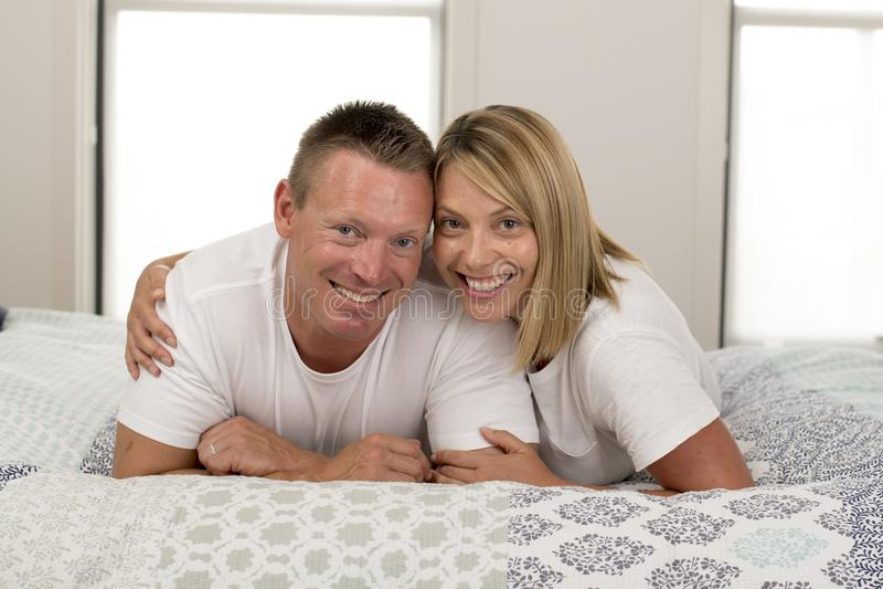 年轻美好和光芒四射的浪漫夫妇30到40岁微笑愉快在摆在甜点和拥抱的爱在家说谎在床上 库存图片