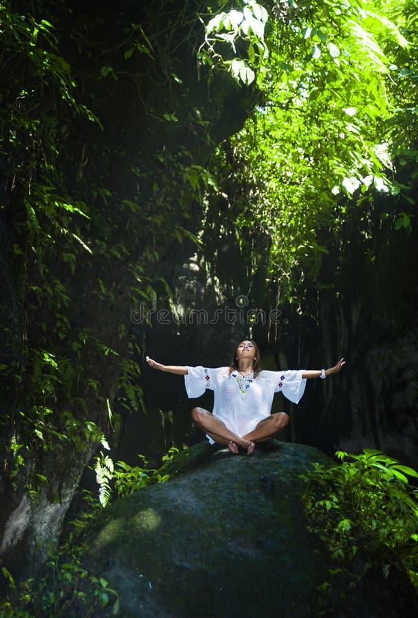 年轻美好和愉快的亚洲实践的瑜伽户外在使坐在岩石的平安和新热带背景惊奇做r 免版税库存图片