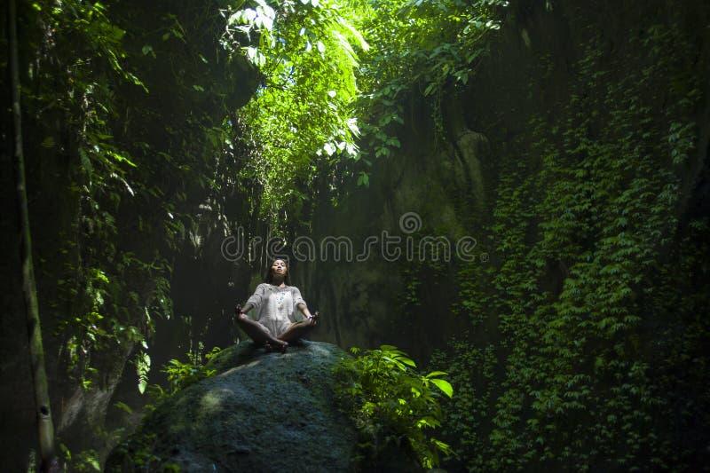 年轻美好和愉快的亚洲实践的瑜伽户外在使坐在岩石的平安和新热带背景惊奇做r 库存照片