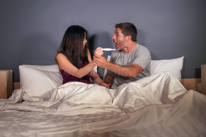 年轻美好和愉快的夫妇一起在看在妊娠试验的床上正面结果与妻子或女朋友怀孕的sur 免版税图库摄影