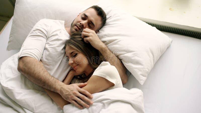 年轻美好和爱恋的夫妇亲吻并且拥抱入床,当醒早晨时 可爱的人顶视图  免版税库存图片