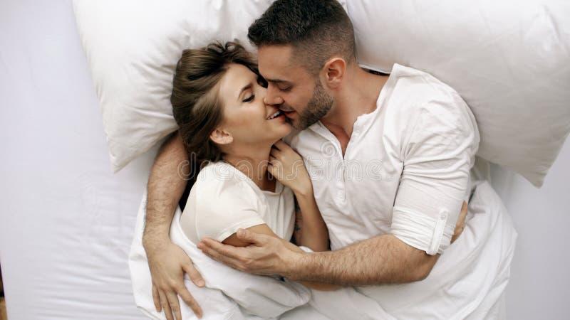 年轻美好和爱恋的夫妇亲吻并且拥抱入床,当醒早晨时 可爱的人顶视图  免版税库存照片