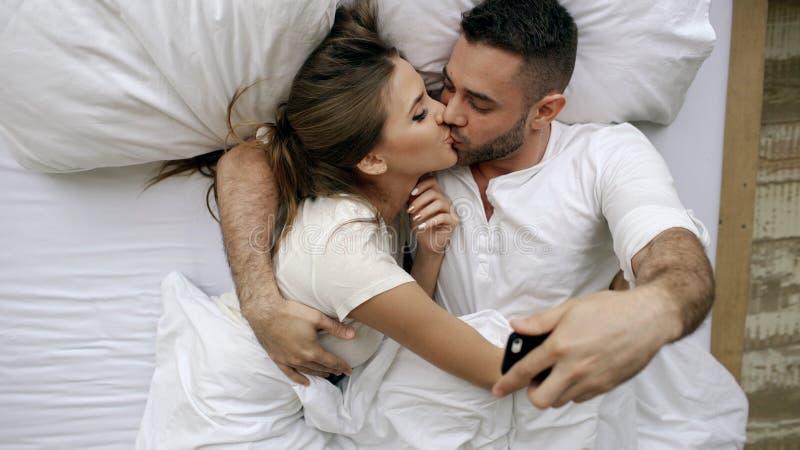 年轻美好和爱恋的夫妇拍在智能手机照相机的selfie照片并且亲吻,当在床上在早晨时 库存照片
