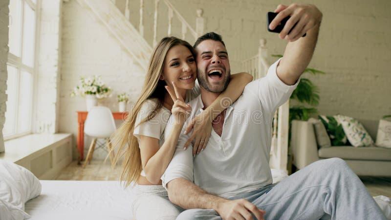 年轻美好和爱恋的夫妇拍在智能手机照相机的selfie照片,当坐在床上在早晨时 免版税库存图片
