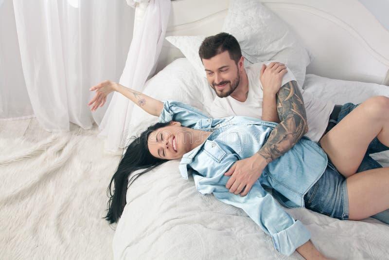 年轻美好和爱恋的夫妇拍在智能手机照相机的selfie照片,当坐在床上在早晨时 免版税库存照片