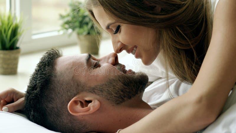 年轻美好和爱恋的夫妇特写镜头充当并且亲吻床在早晨 亲吻和拥抱他的可爱的人 免版税图库摄影