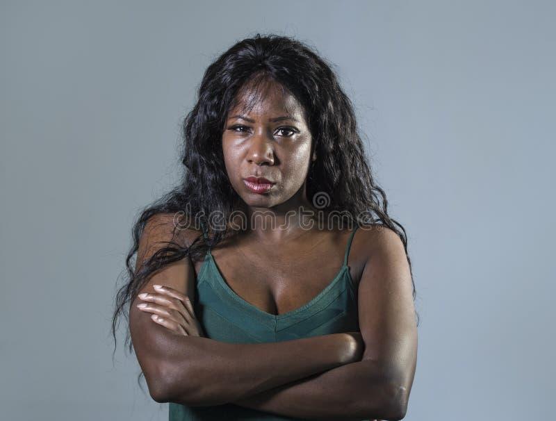 年轻美好和被注重的黑非裔美国人的妇女感觉生气和恼怒看起来严肃和小便的摆在与被折叠的ar 库存照片