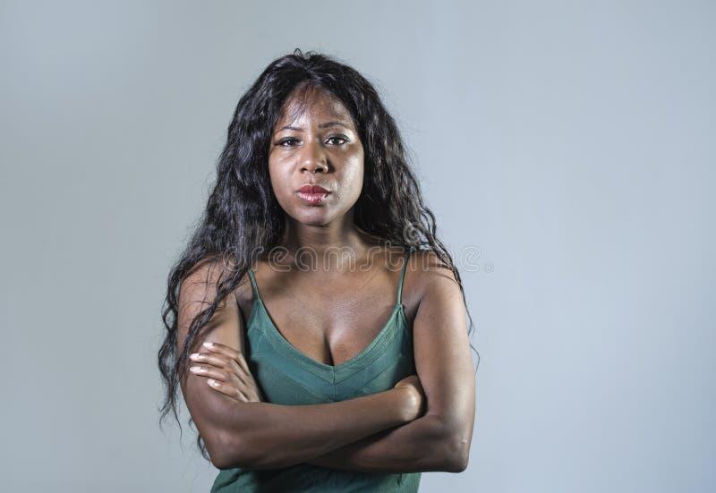 年轻美好和被注重的黑非裔美国人的妇女感觉生气和恼怒看起来严肃和小便的摆在与被折叠的ar 免版税库存图片