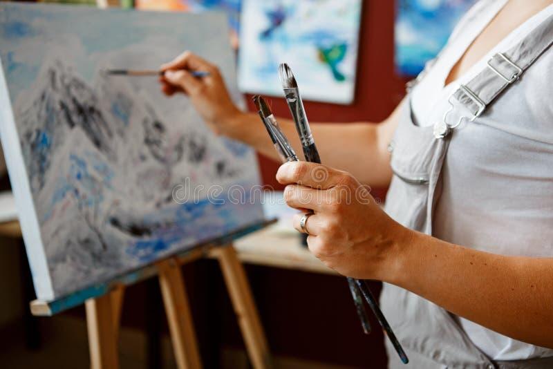 年轻美好的中年白色白种人妇女艺术家图画绘画特写镜头与丙烯酸漆的在帆布 库存图片