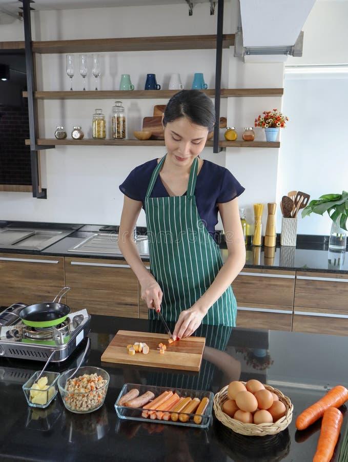 年轻美好的亚洲妇女woth微笑切在木板材的香肠 图库摄影