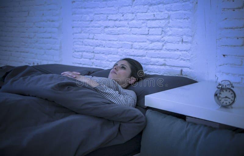 年轻美好的哀伤和担心的拉丁妇女遭受的失眠和无法失眠的问题在晚上说谎的o后睡觉 免版税库存图片