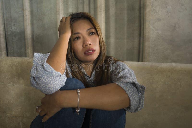 年轻美好的哀伤和沮丧的妇女周道和迷茫的在家长沙发感觉伤心遭受的消沉危机和 免版税库存图片