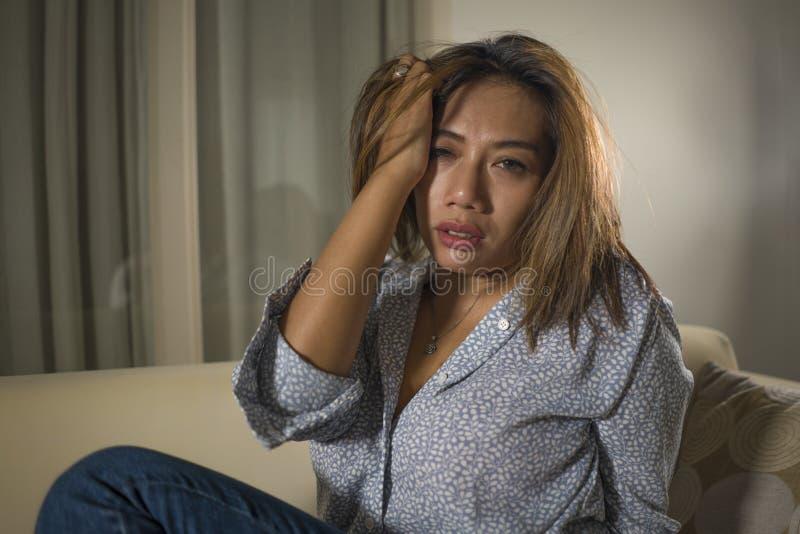 年轻美好的哀伤和沮丧的妇女周道和迷茫的在家长沙发感觉伤心遭受的消沉危机和 免版税库存照片