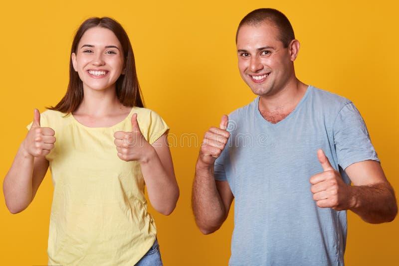 年轻美好的夫妇半身画象在黄色演播室背景的 妇女和男性在偶然衬衣庆祝 库存照片