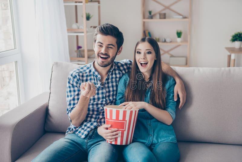 年轻美好的夫妇观看电影户内在家,吃 免版税库存图片