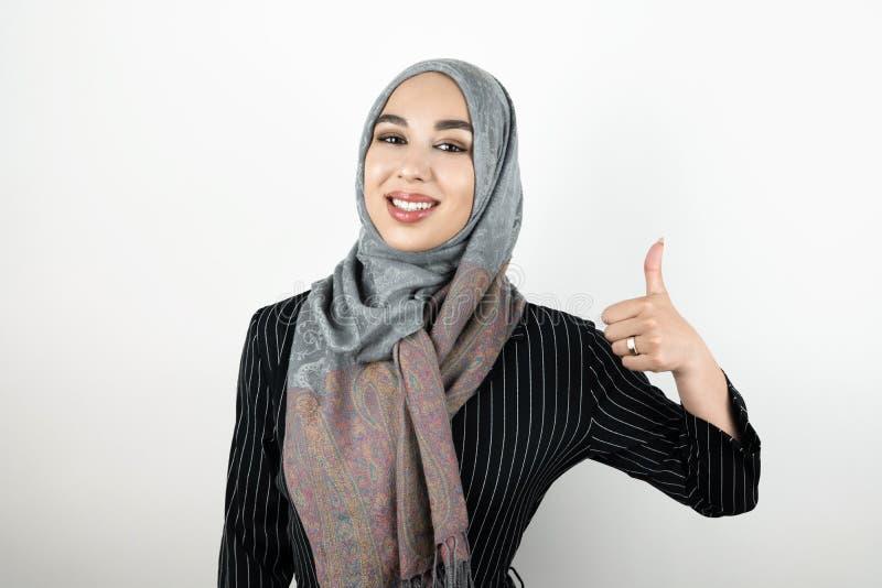年轻美好的微笑的正面回教妇女佩带的头巾hijab头巾陈列ok标志被隔绝的白色背景 库存图片