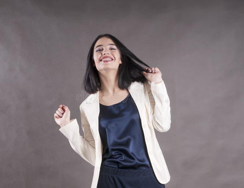 年轻美好的愉快的女实业家表示支撑深色的演播室 图库摄影
