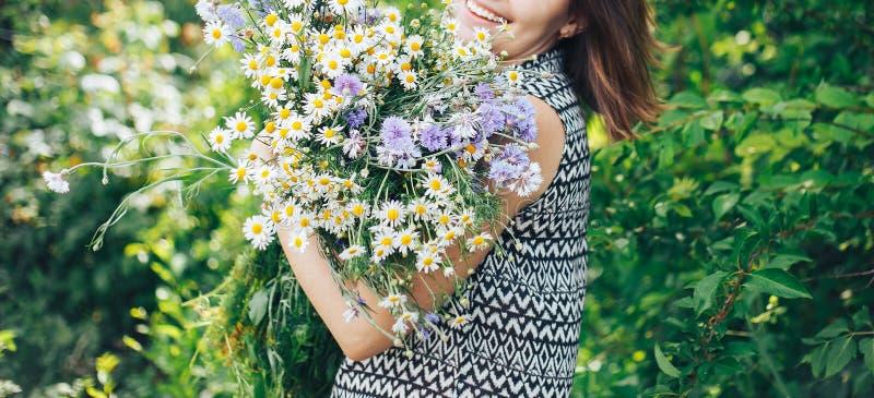 年轻美好的狂放的领域妇女女孩举行大花束开花 库存图片