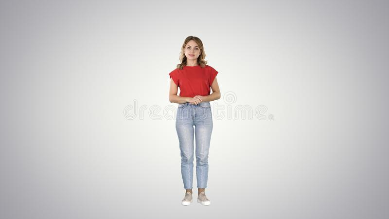 年轻美好的逗人喜爱的快乐的妇女身分和看等待某事在梯度背景的照相机 免版税图库摄影