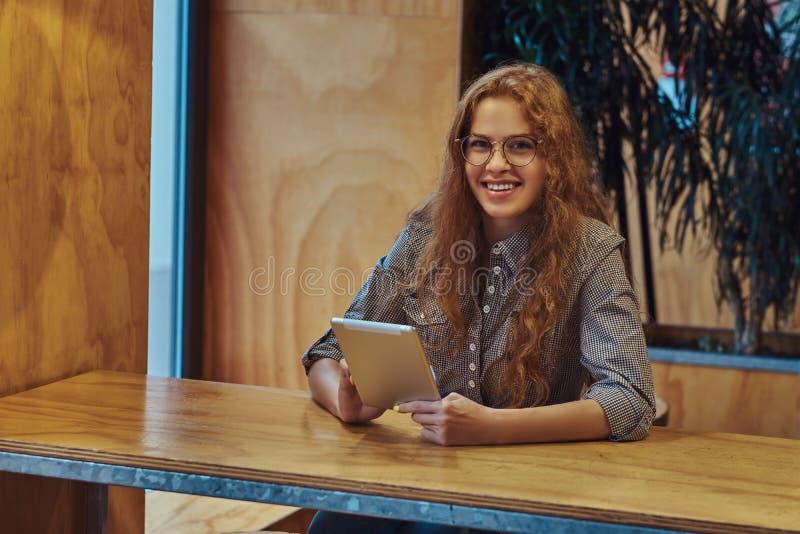 年轻聪明的红头发人卷曲女学生拿着一种数字式片剂,当坐在学院军用餐具的一张桌上在a期间时 库存照片