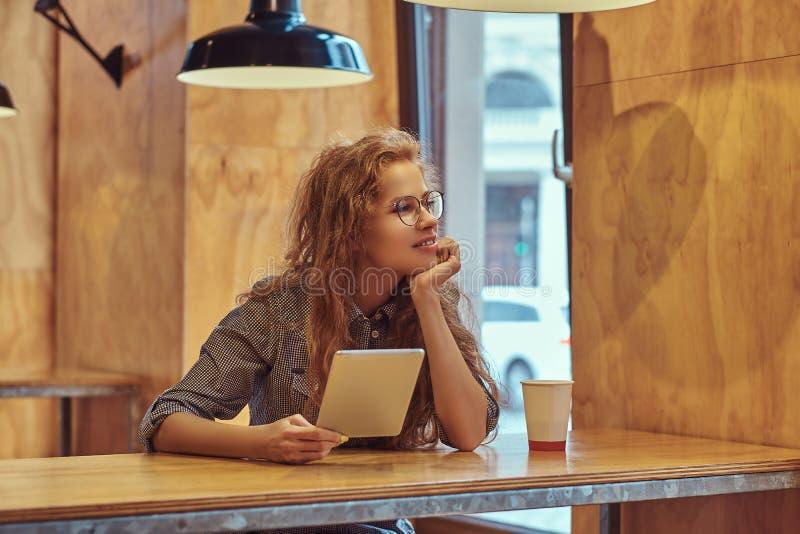 年轻聪明的红头发人卷曲女学生拿着一种数字式片剂,当坐在学院军用餐具的一张桌上在a期间时 免版税库存图片