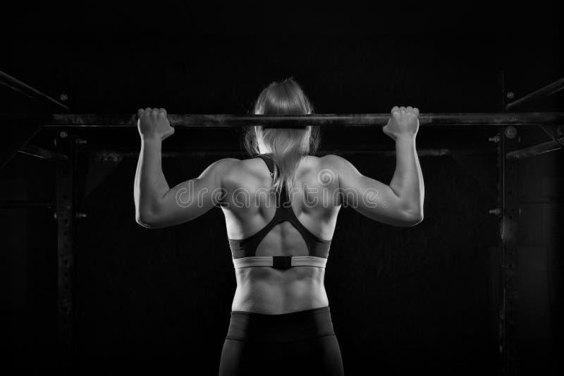 年轻肌肉妇女做拔在健身房的锻炼 免版税库存图片
