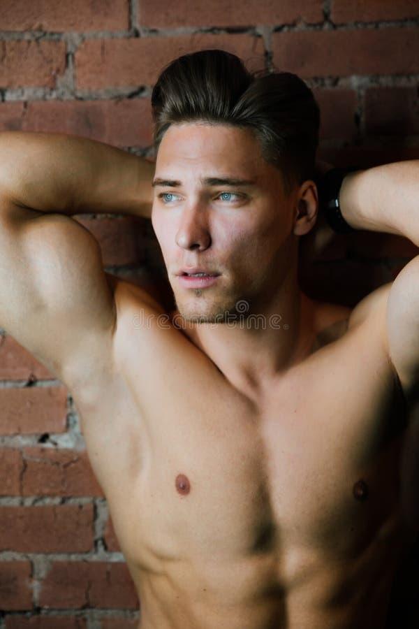 年轻肌肉爱好健美者健身式样摆在反对砖墙顶楼健身俱乐部 秀丽圆环闪光 免版税图库摄影