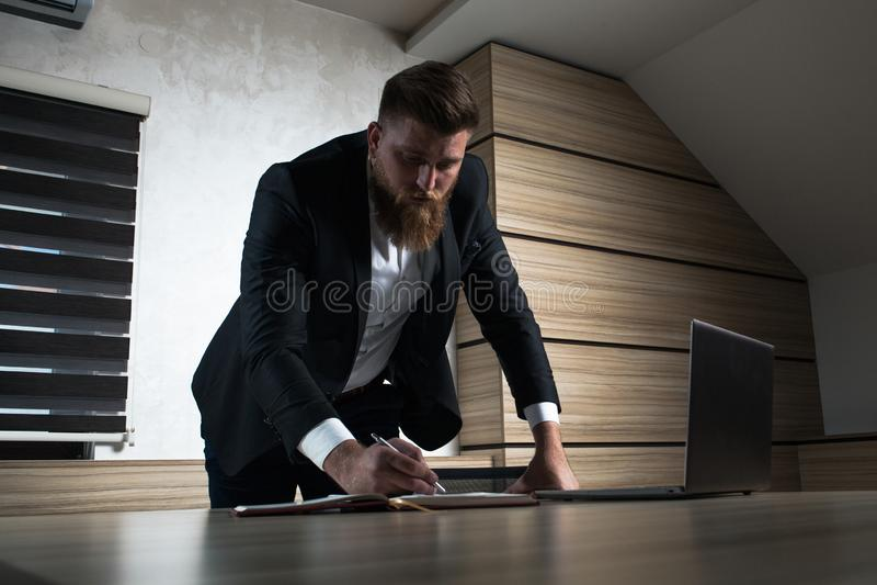 年轻胡子商人夜间工作在办公室 免版税图库摄影