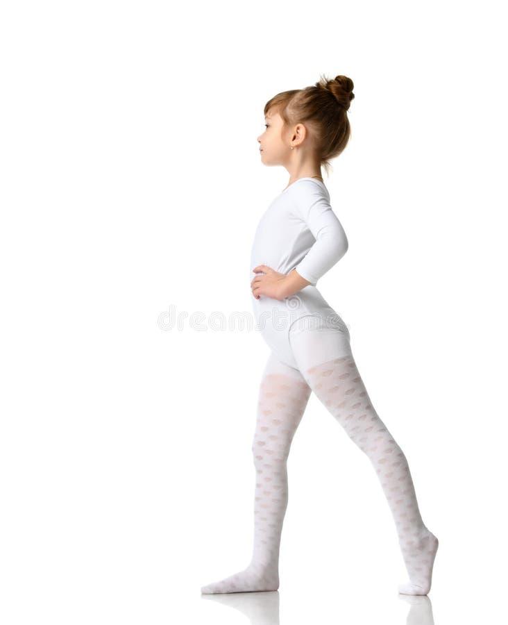 年轻舒展在白色运动身体布料的体育深色的女孩锻炼锻炼 免版税库存图片