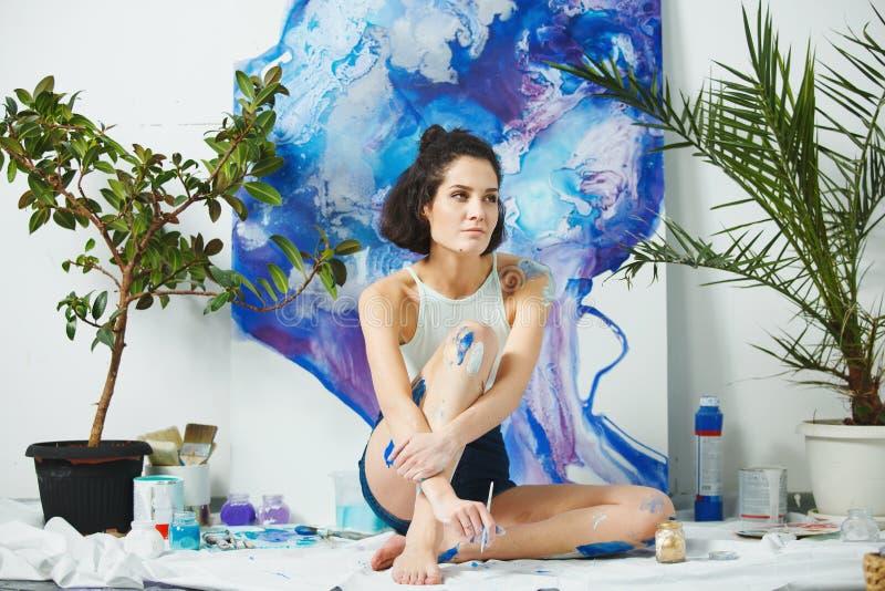 年轻艺术家创造新的艺术品坐地板 严重的妇女 免版税库存照片