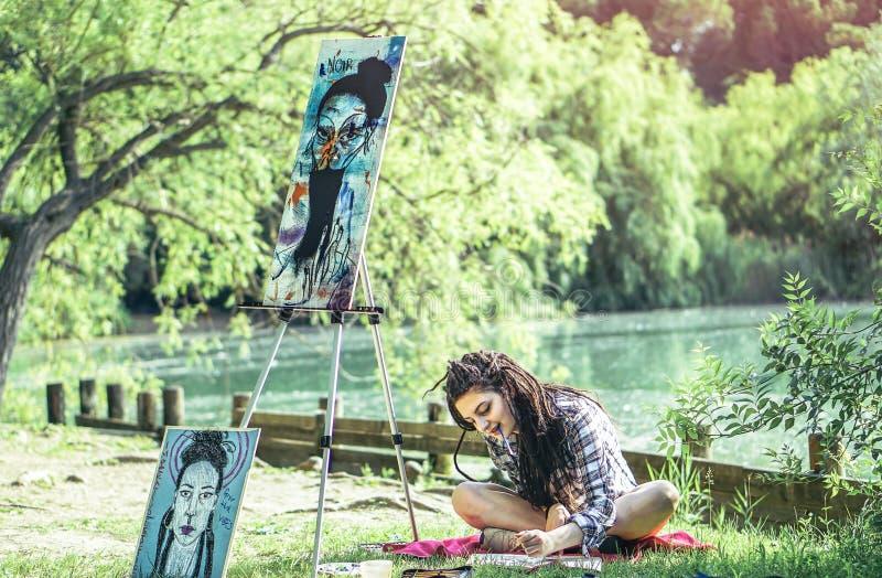 年轻艺术家女孩图画草稿在湖-有dreadlocks发型工作的画家妇女附近的公园在她的在自然的艺术 免版税库存图片