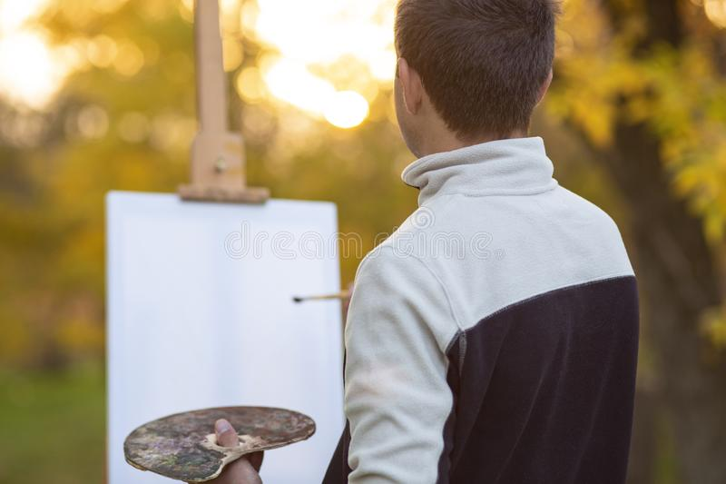 年轻艺术家绘在帆布的一幅画在一个画架本质上,有刷子的一个人和油漆调色板在秋天树中的, 图库摄影