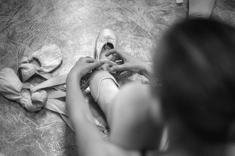 年轻芭蕾舞女演员佩带的pointe鞋子 一位芭蕾舞女演员的特写镜头在舞厅里 免版税图库摄影