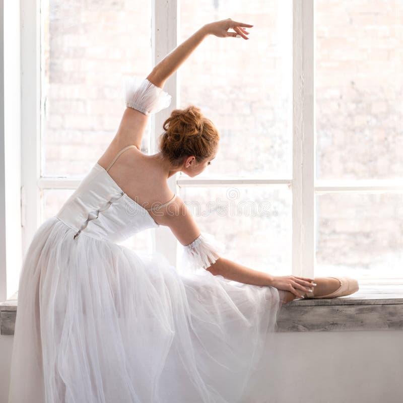 年轻芭蕾舞女演员在舞厅舒展 库存图片