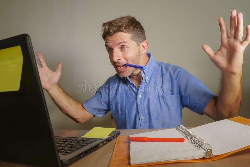 年轻英俊和愉快的商人在家与便携式计算机办公室打手势一起使用快乐和激动在企业家s 免版税库存照片