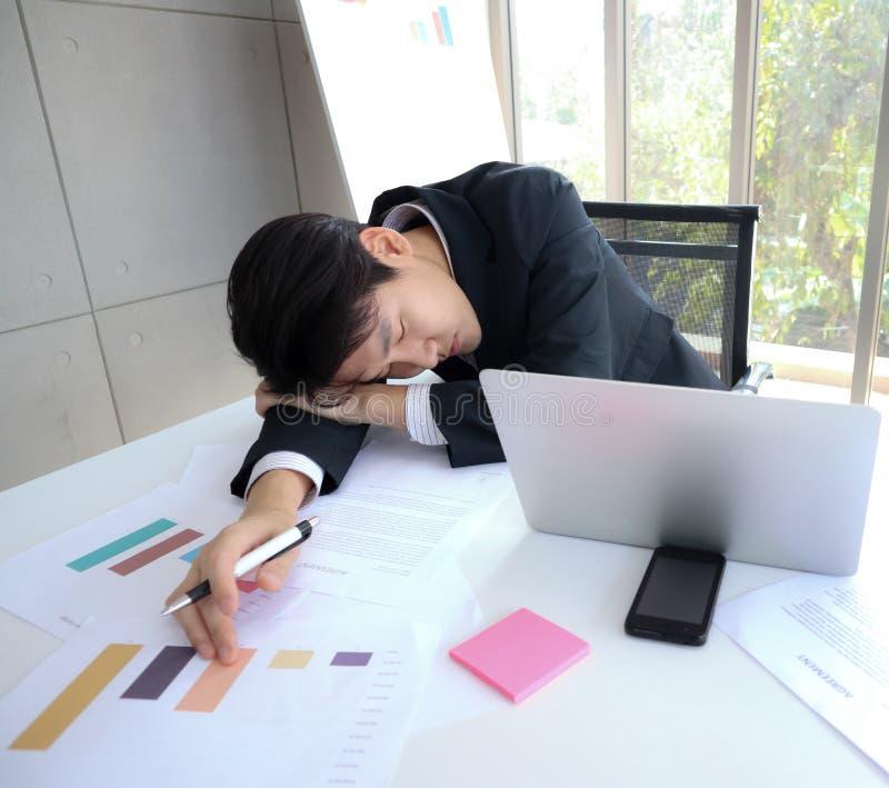 年轻英俊的亚裔商人睡着在运转的书桌上 免版税图库摄影
